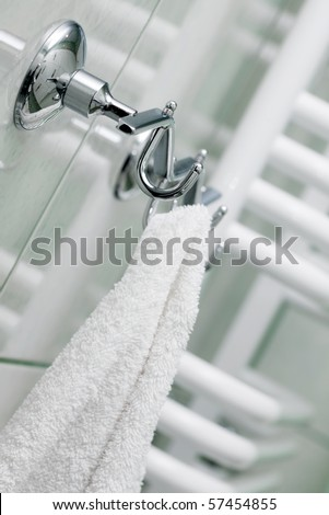 The towel hangs on a hanger in a bathroom - stock photo
