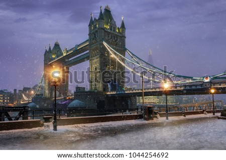 The Tower Bridge by night during winter time with falling snow, London, UK