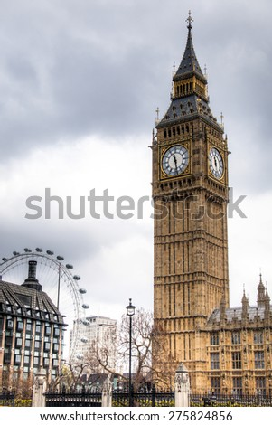 The tower containing the Big Ben Bell, at the corner of the parliament with the London Eye wheel in the background in London, capital of the United Kingdom  - stock photo