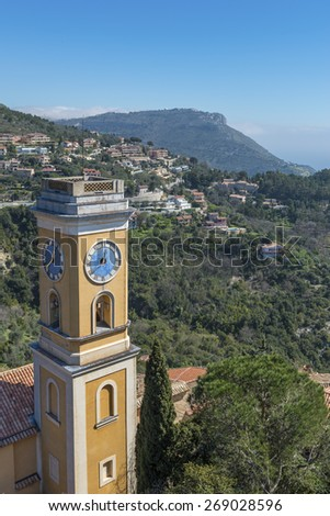 The tower of the church in Eze Village dedicated to Our Lady of the Assumption. Looking out to the coast towards Monaco - stock photo