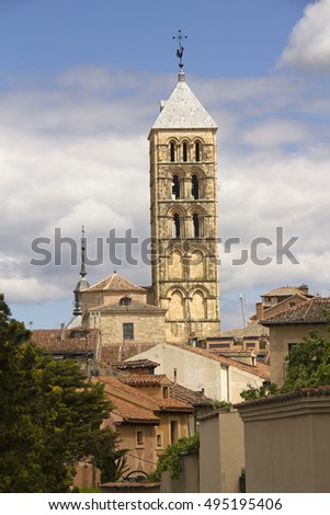 The tower of the San Esteban Church above the roofs of historical houses in Segovia, Spain