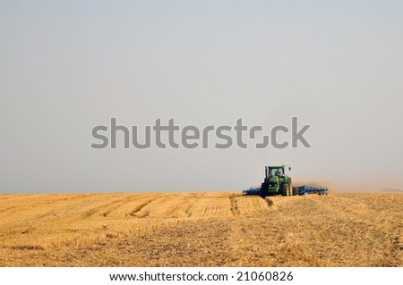 The tractor makes processing of a ground after wheat harvesting - stock photo