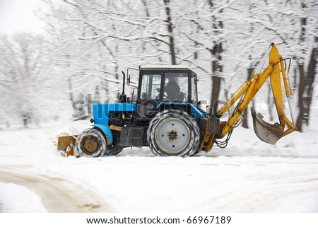 The tractor of dark blue color deletes snow in park - stock photo