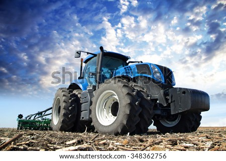 The tractor wheels on the huge field, a farmer riding a tractor, a tractor working in a field agricultural machinery in the work, tractor in the background cloudy sky - stock photo