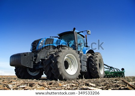 The tractor wheels on the huge field, a farmer riding a tractor, a tractor working in a field agricultural machinery in the work, tractor against the blue sky - stock photo