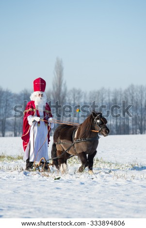 The traditional feast of St. Nicholas in Czech Republic: St.Nicholas on a sleigh with a pony in harness - stock photo