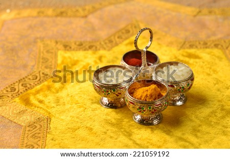 "The traditional Kumkum  powder and rice grains in a tiny silver container.  Kumkum is used as a ""Tilak"" in India at auspicious occasion. - stock photo"