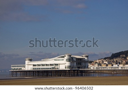 The traditional seaside pier with the hinterland on the horizon at Weston-super-Mare in the Bristol Channel UK on a winter morning - stock photo