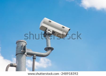 The traffic security CCTV camera operating on road detecting traffic. - stock photo