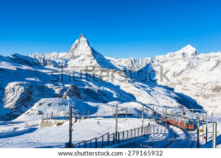 The train running to the Gornergrat station in the famous touristic place with clear view to  Matterhorn. - stock photo