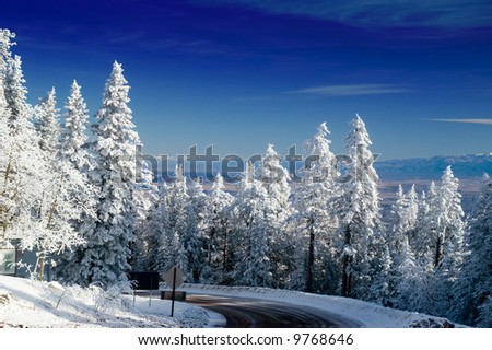 The Tramway Road leads up to the top of the Sandia Mountains outside of Albuquerque, New Mexico, as winter still remains - stock photo