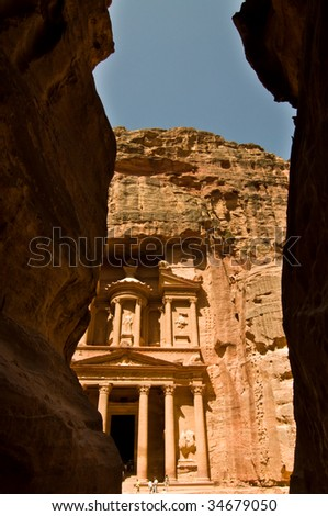 The Treasury seen through the Siq, a narrow canyon path through high rock cliffs, at Petra, Jordan.