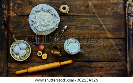 The trendy bakery chef laid on the table ingredients for bagels fresh fruit. On the table are the products for baking flour, eggs, milk and fresh fruit - stock photo