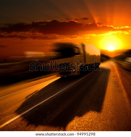 The truck on highway. A sunset.