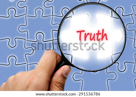 The truth uncovered word. Magnifier and puzzles. - stock photo