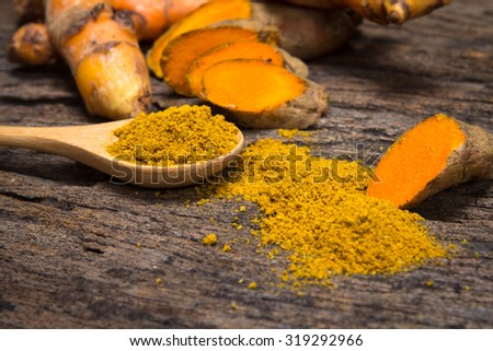 the turmeric powder in spoon and roots on wooden plate - stock photo