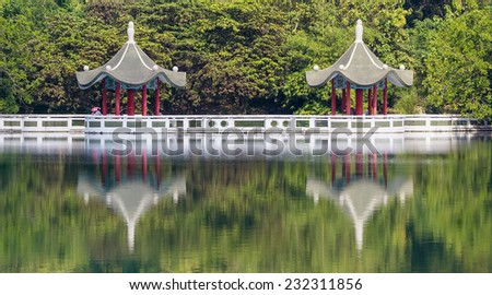 The Twin Lotus Pavilion with Tourists in The Forest, With Reflections from The Green Lake, Located  in Cheng Ching Lake, Kaohsiung, Taiwan.  - stock photo