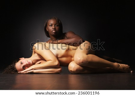 The two beautiful naked women are hugging each other black and white - stock photo
