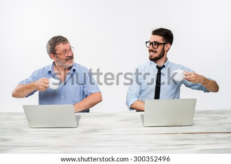 The two colleagues working together at office on white  background. both happy men are getting good news. concept of  success in business. they rejoicing and clinking cups  - stock photo