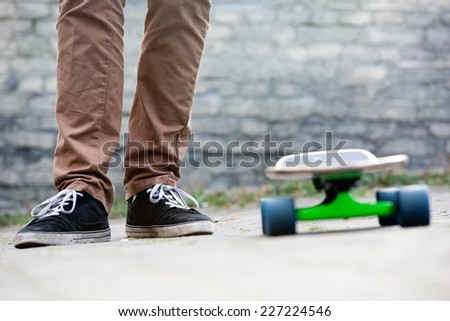 The two feet of a casually dressed man standing next to a skateboard in an urban setting, with a brick wall in the background. All earthy tones - stock photo