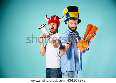 The two football fans with mouthpiece over blue - stock photo