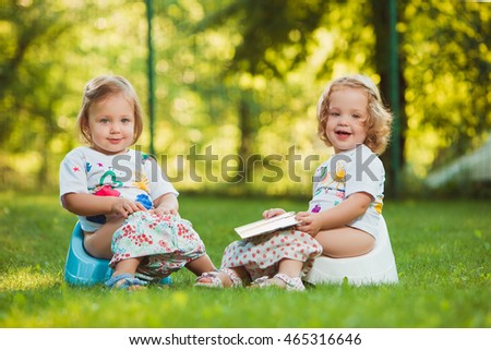 The two little baby girls sitting on pots