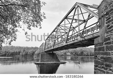 The Uhlerstown-Frenchtown Bridge from Frenchtown, New Jersey to Uherlstown, Pennsylvania. The bridge crosses the Delaware River. The photo is in black and white. - stock photo
