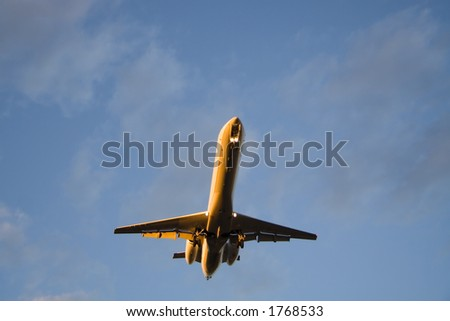 The underside of a landing Embraer illuminated by the setting sun. - stock photo