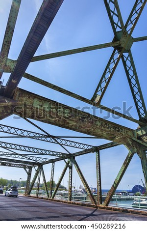 The underside view of an old rusted bridge in Toronto against blue sky.