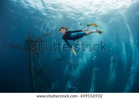 The underwater scenes. Lady the diver swims underwater by sunken ship - stock photo
