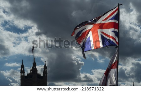 The Union Jack and flag of St George fly over a souvenir stall on Westminster Bridge. The houses of Parliament in the background - stock photo