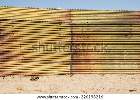 the United States border with Mexico near Algodones with a metal fence barrier - stock photo