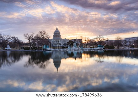 The United States Capitol building in Washington DC at sunrise mirrored in the reflecting pool - stock photo