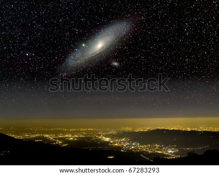 The Universe above city lights. The Andromeda galaxy. - stock photo