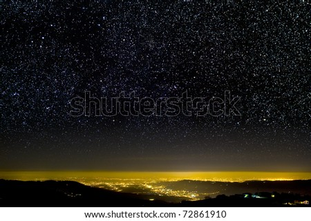 The Universe above city lights. The starry night sky. - stock photo