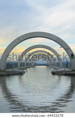 The upper canal approach to the Falkirk Wheel, Scotland.  This futuristic construction is the world's only rotating boat lift.  Taken in early evening. - stock photo