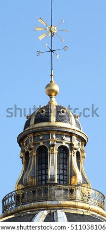 The upper tower of the French Academy with a spire and golden weather vane. Paris. France. Summer.