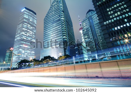 The urban background of modern office buildings car night light trails in Shanghai - stock photo