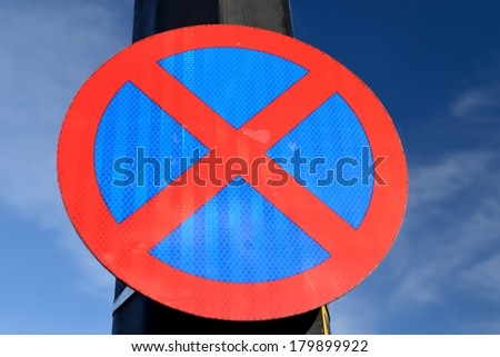 The urban clearway sign with blue skies in the background. - stock photo