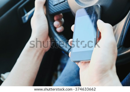 The use of mobile phones in the car. urban lifestyle background.