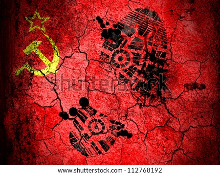 The USSR flag painted on  cracked ground with vignette with dirty oil footprint over it - stock photo