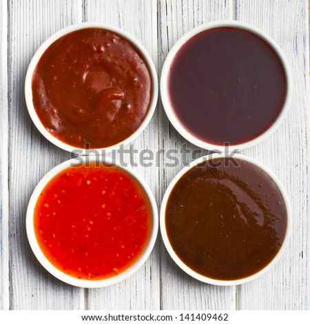 the various barbecue sauces in ceramic bowls - stock photo