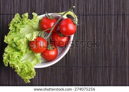 The vegetables on the table. Tomatoes and leaf lettuce. Dietary food. Delicious fresh and juicy vegetables. Red tomatoes on a branch. Farming. Round tomatoes. Vegetables on a dark background.  - stock photo