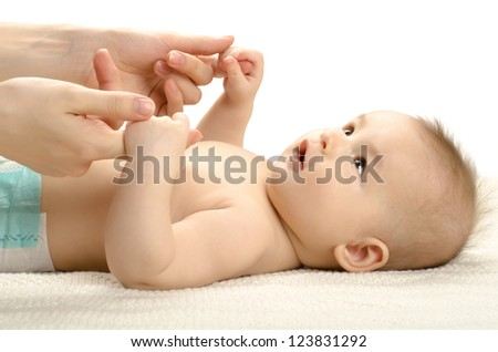 the very beautiful fun little baby  lie on light bedding - stock photo