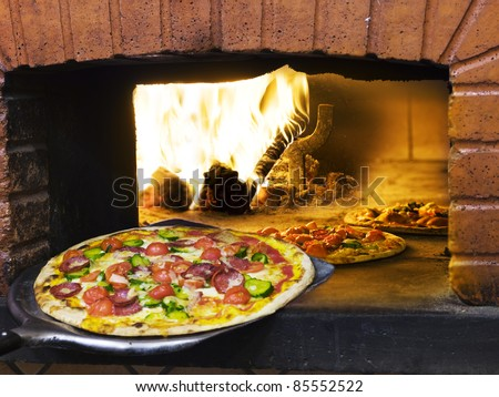 the very italian pizza coming out of a wood burning pizza oven. - stock photo