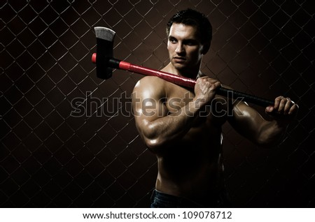 the very muscular guy on dark  brown netting background  with big axe - stock photo
