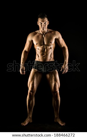 the very muscular handsome sexy guy on black background, full-length