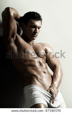 the very muscular handsome sexy guy on   grey background, strict - stock photo