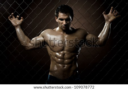 the very muscular handsome sexy guy ,  on  netting   steel fence - stock photo