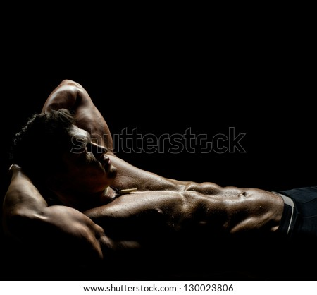 the very muscular sleeping sexy guy, lying on black background, naked  torso - stock photo